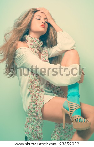 Beautiful young woman sitting in a trendy shoes - stock photo
