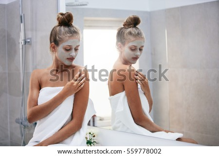 Beautiful young woman sitting in bathroom by the mirror with face mask   Female doing skin. Woman In Bathroom Stock Images  Royalty Free Images   Vectors