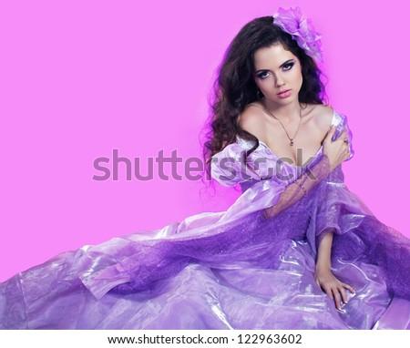 Beautiful young woman sitting in fashion dress - stock photo