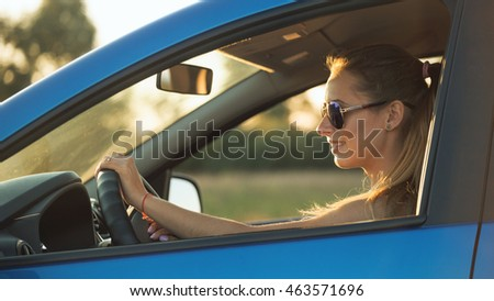 Beautiful young woman sitting in the car driving into the sunset.
