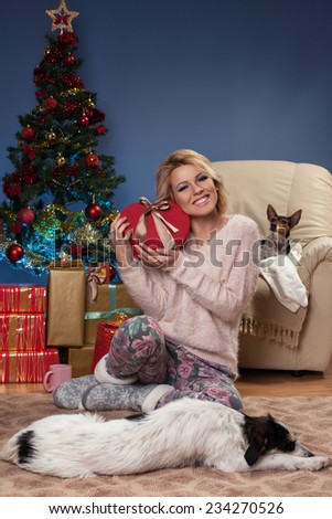 Beautiful young woman sitting near Christmas tree and holding a gift in arms with the dog in front of her who sleeps on the floor. - stock photo