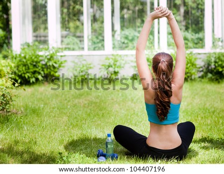 Beautiful young woman sitting near the bottle with water on green grass at park - stock photo