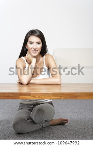 Beautiful young woman sitting next to a coffee table at home in casual clothes - stock photo