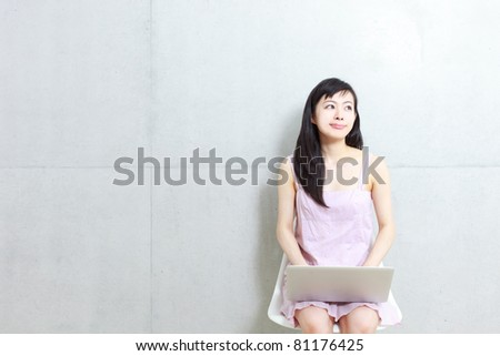 Beautiful young woman sitting on a chair with laptop computer. - stock photo