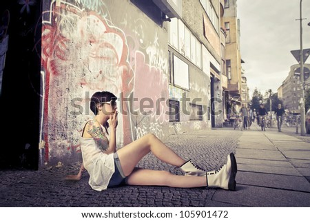 Beautiful young woman sitting on a city street and smoking a cigarette - stock photo