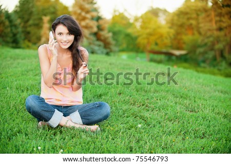 Beautiful young woman sitting on a green lawn in the lotus position and talking on a cell phone - stock photo