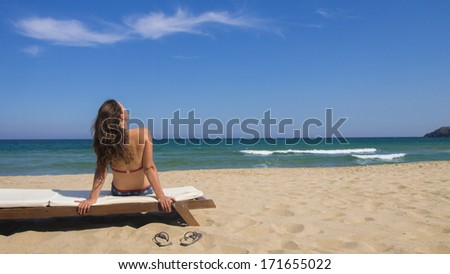 Beautiful young woman sitting  on a lounge and enjoying the view at the beach on a beautiful sunny day. - stock photo