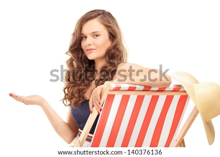 Beautiful young woman sitting on a sun lounger and gesturing with hand, isolated on white background - stock photo