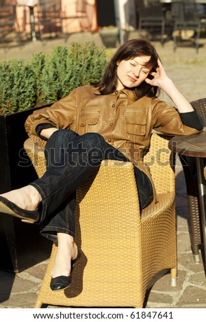beautiful young woman sitting on a wicker chair - stock photo