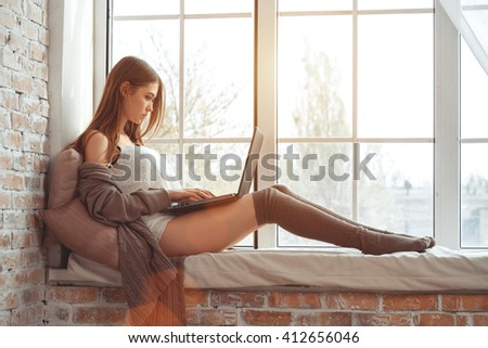 Beautiful Young Woman Sitting On A Windowsill With Notebook
