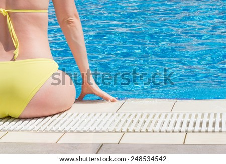 Beautiful Young Woman Sitting On Edge Of The Pool - stock photo