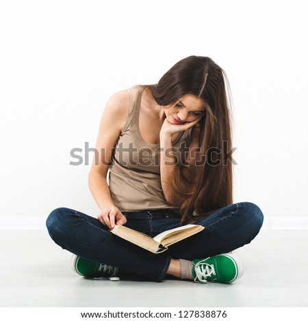 Beautiful young woman sitting on floor with book - stock photo