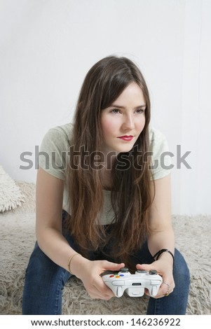 Beautiful young woman sitting on fur sofa with game controller - stock photo
