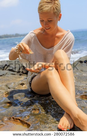 Beautiful young woman sitting on picturesque rocky seashore pouring water from seashell - stock photo