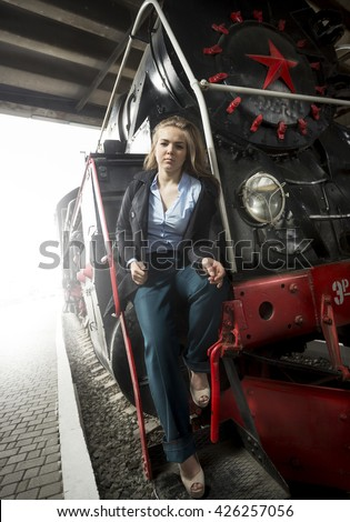 Beautiful young woman sitting on stairs of old steam train - stock photo