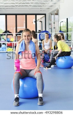 Beautiful young woman sitting on the blue pilates ball and smiling. Group of female athletes sitting behind.