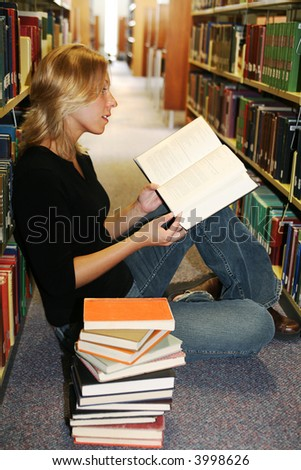 Beautiful young woman sitting on the floor in the library with a stack of books, reading with interest - stock photo