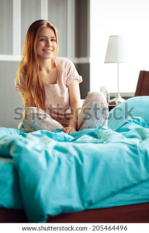 Beautiful young woman sitting on unmade bed in the morning - stock photo
