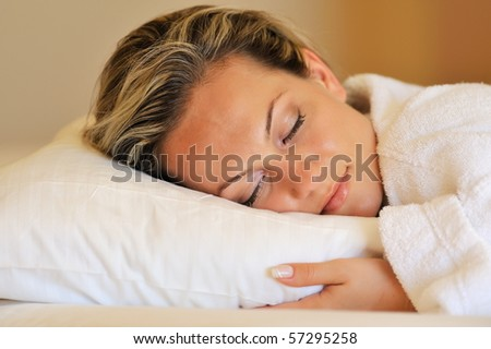 Beautiful young woman sleeping in her bed - stock photo