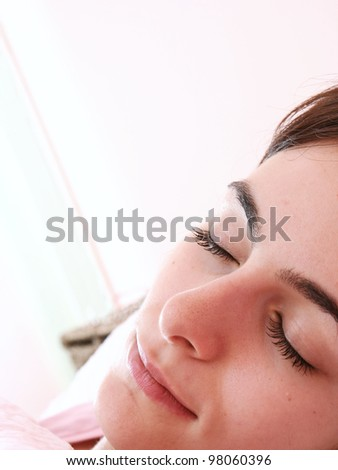 Beautiful young woman sleeping on bed in her bedroom at home in the morning. - stock photo