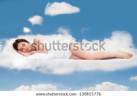 Beautiful Young Woman Sleeping On Clouds In Sky - stock photo