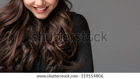 Beautiful young woman smile on gray background.  - stock photo