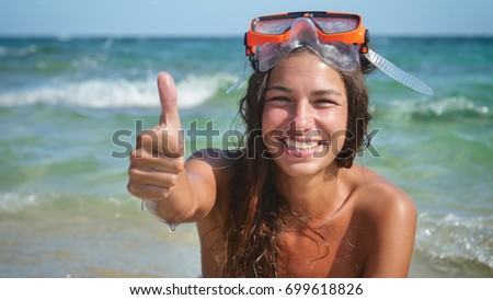Beautiful young woman smiles at the sea, happy in a swimsuit wearing a diving mask.