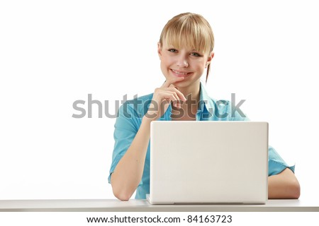Beautiful young woman smiles while sitting at a laptop computer. Lots of copyspace - stock photo