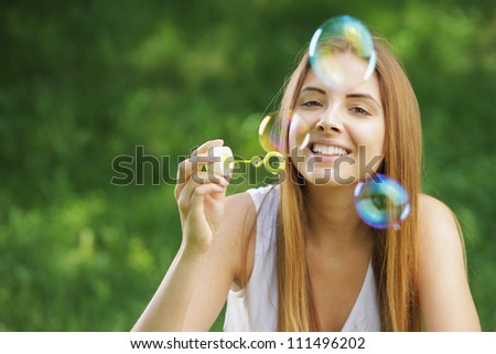 Beautiful young woman smiling and blowing bubbles outdoor in the nature.