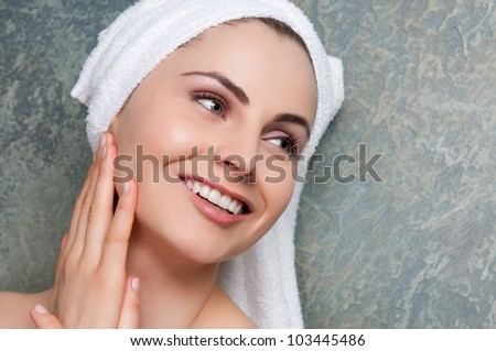 Beautiful young woman smiling and relaxing at spa center - stock photo