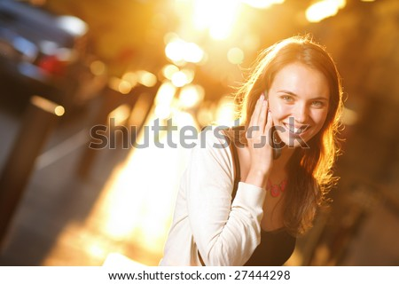 Beautiful young woman smiling and talking on cell phone on sunny street. ShallowDOF. - stock photo