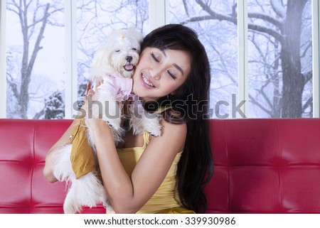 Beautiful young woman smiling happy while hugging her dog on the sofa, shot at home - stock photo