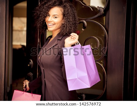 Beautiful young woman smiling holding colorful shopping bags - stock photo