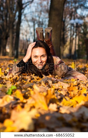 Beautiful young woman smiling lying down in autumn leaves in park