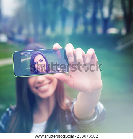 Beautiful young woman smiling taking a selfie with smartphone outdoors in park in spring. Closeup, selective focus on phone, instant filter look, retouched, noise added, square format.  - stock photo