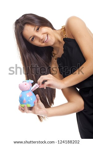 beautiful young woman smiling with a cow piggy bank... - stock photo