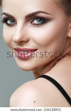 beautiful young woman smilling with evening make up, perfect skin. Trendy smoky eyes - stock photo