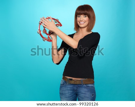 beautiful, young woman smilng, playing a red tambourine, on blue background