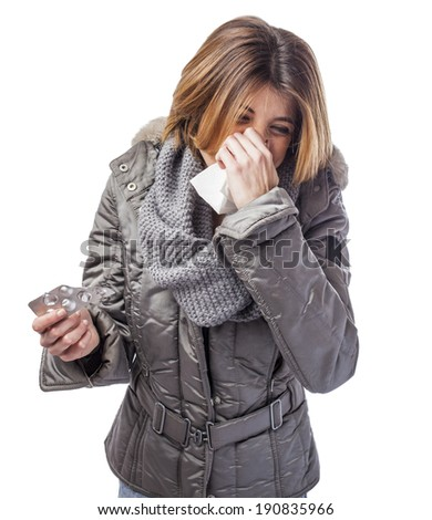 beautiful young woman sneezing and holding medicines - stock photo