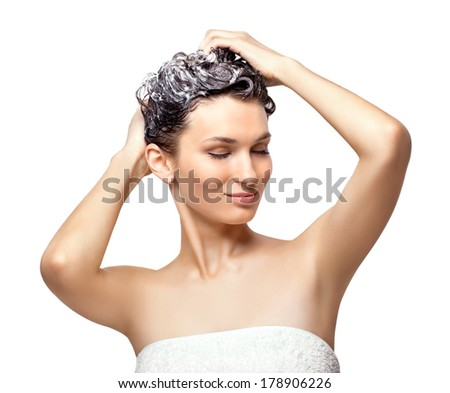 Beautiful young woman soaping her head, isolated on white - stock photo