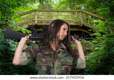 Beautiful young woman soldier with a M16 rifle - stock photo