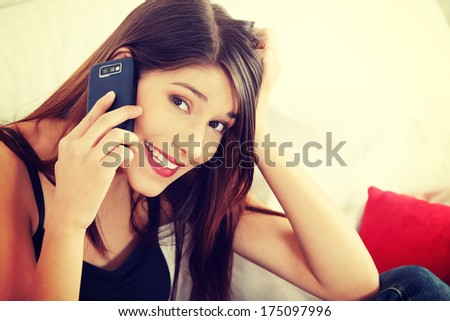 Beautiful young woman speaking by mobile phone - indoors  - stock photo