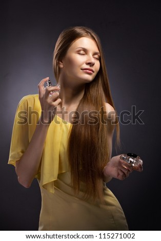 beautiful young woman spraying perfume on gray dark  background - stock photo