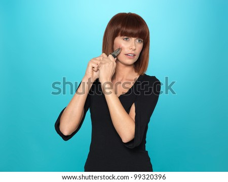 beautiful, young woman squeezing a pimple with a pliers, on blue background