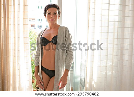 Beautiful young woman standing by a bright window with curtains in a home bedroom during a sunny day, home interior. Wellness, well being and care lifestyle at home, indoors. Sensual body figure.  - stock photo