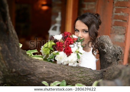 beautiful young woman standing by a tree posing with a bouquet of roses