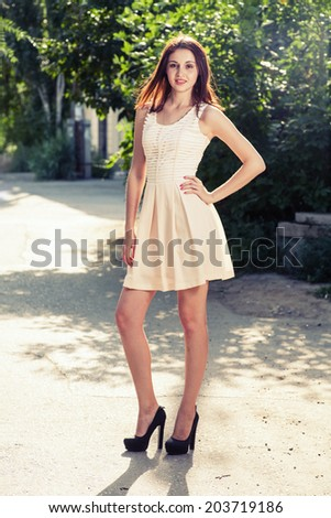 Beautiful young woman standing in a street  At Sunset full body shot - stock photo