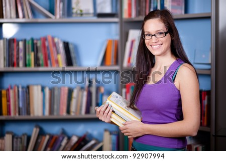 Beautiful young woman standing in front of bookshelves in a library/bookstore - stock photo