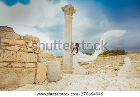 beautiful young Woman standing inside ancient ruins on a Greek ionic pole ,wearing White and Gold Greek Costume.