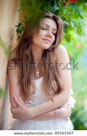 Beautiful young woman standing near wall and green leaves
